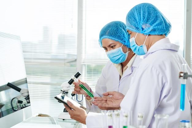 Работники лаборатории с пробиркой зеленой жидкости
