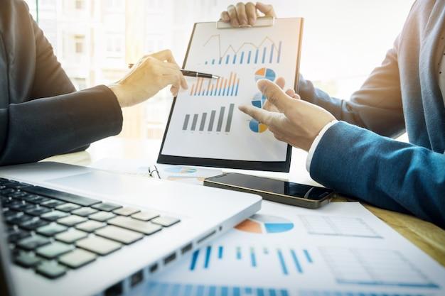 Командный процесс. команда молодых бизнес-менеджеров, работающих с новым проектом запуска. labtop на деревянном столе, клавиатура, текстовое сообщение, анализ графиков.