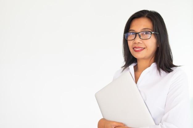 白い背景の上のlabtopのノートを保持している眼鏡をかけている女性実業家