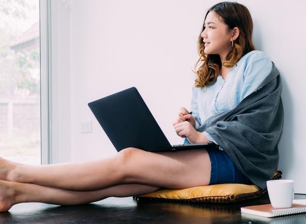 Довольно азиатская женщина интернет онлайн работать дома и расслабиться образ жизни с ее labtop