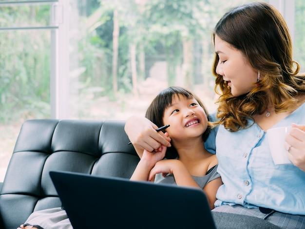 子供とお母さんがlabtopを見ていると一緒に幸せを感じる