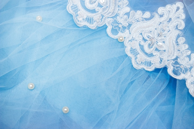 Lace on blue tulle with beads. sewing a wedding dress. wedding concept