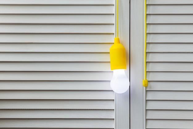Кружева лампочка светится на белом деревянном фоне