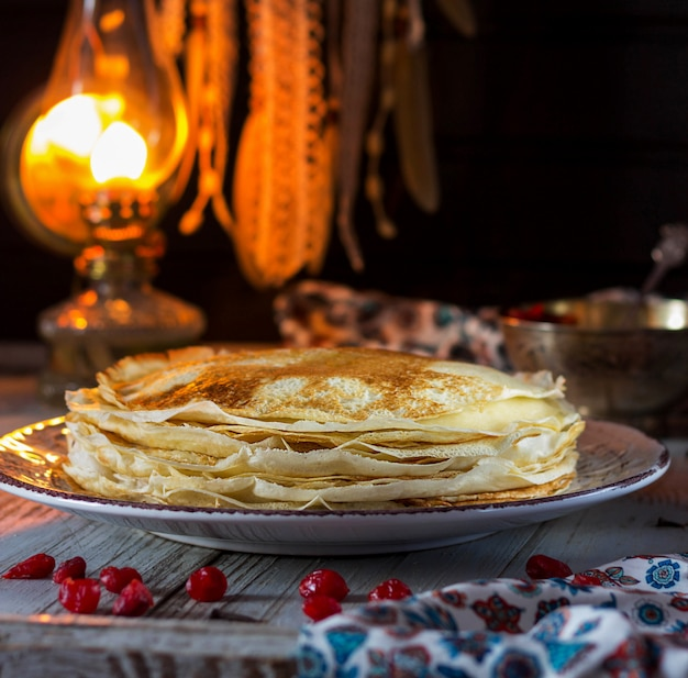Lace pancakes and cherry on the table. pancake week
