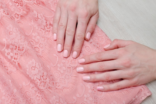 Lace pink  blouse and female hands. pink manicure