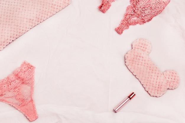 Комплект кружевного белья, подушки, маска для глаз, духи на домашней кровати утром. романтический стиль. плоская планировка и копирование пространства.