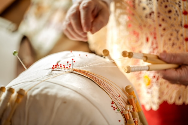 Lace weaving on bobbins is an old russian folk craft. hands lace attached needles for weaving lace pattern.