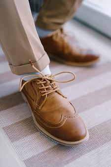 신랑 다리 근접 촬영에 끈으로 묶인 갈색 브로그