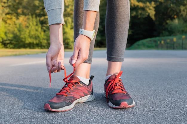 ランニングシューズをひもで締めます。公園で屋外のトレーナーをひもで締める女性の手のクローズアップ