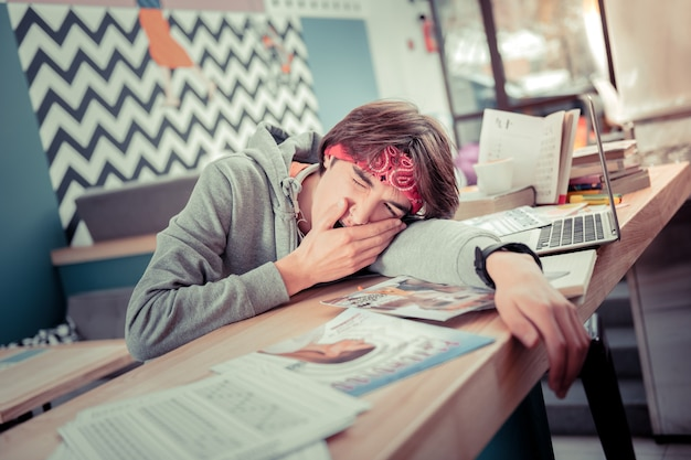 The lack of energy. the tired student yawning and lying on the table
