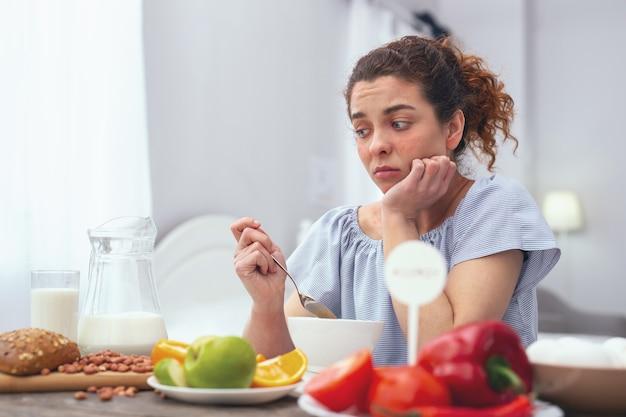 食欲の欠如。スプーンを持って朝食のテーブルに座って、自分自身を食べさせようとしている間がっかりしているように見える若い女性