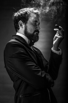 Lack and white portrait of bearded smoking gentleman in a suit