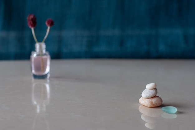 Лаконичный минимализм пирамида из трех камней и стекла за размытой бутылкой розовой жидкости и веточкой