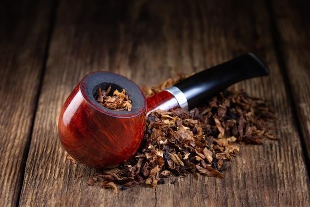 Лакированная курительная трубка и куча табака на старинном деревянном столе.
