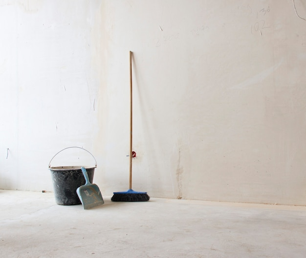 コピースペースのある白い背景の壁にはしごとバケツ。建設中のオブジェクトの概念の背景。