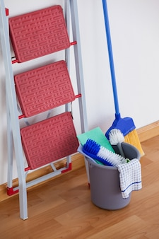 Ladder and cleaning equipment on wooden floor