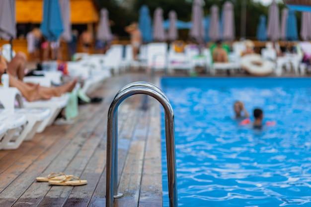 수영장으로 내려가는 사다리 스테인리스 난간. 손잡이가 있는 수영장. 수영장의 사다리입니다. 사람들은 수영장에서 수영하고 휴식을 취합니다.