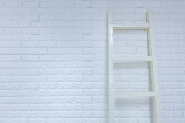 Ladder on white brick wall