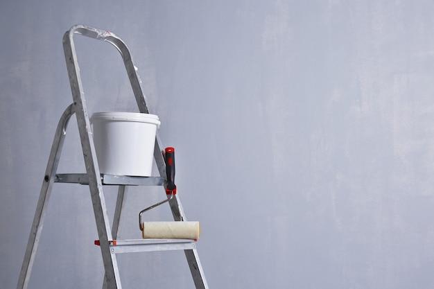 空の部屋に立っているペンキとローラーのはしご