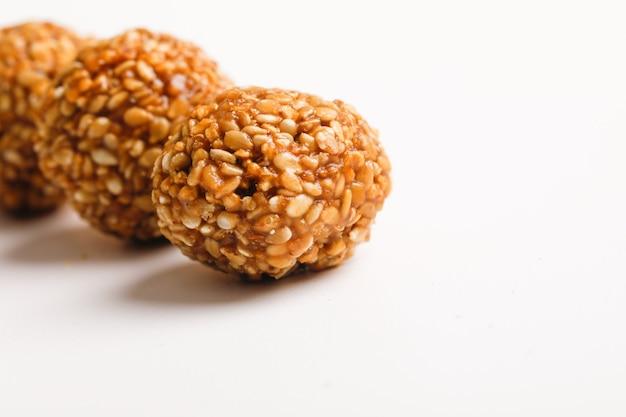 インドの甘い料理、ゴマのボールまたはヒンディー語で呼ばれる、白い背景の上のケladdu