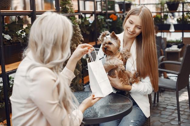 야외 카페에서 숙녀. 테이블에 앉아 여자입니다. 귀여운 강아지와 친구.