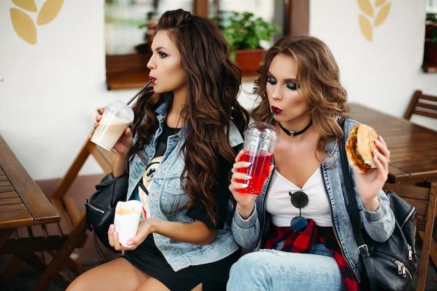 Ladies in cafe drinking lemonade and eating burgers.
