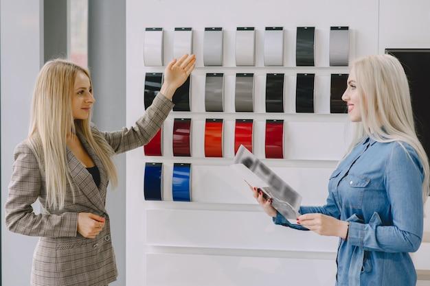 Signore in un salone di automobile. donna che compra l'auto. donna elegante in un vestito blu. il manager aiuta il cliente.