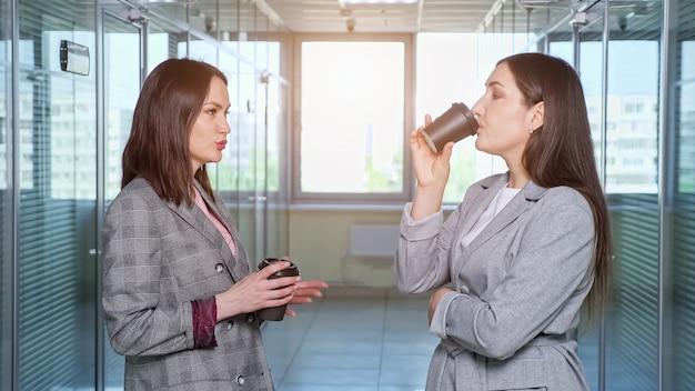 大きな窓のクローズアップに対してオフィスの間のホールで黒いプラスチック製のコップからコーヒーを飲みながら、黒髪の緩い女性の会社のマネージャーが話します