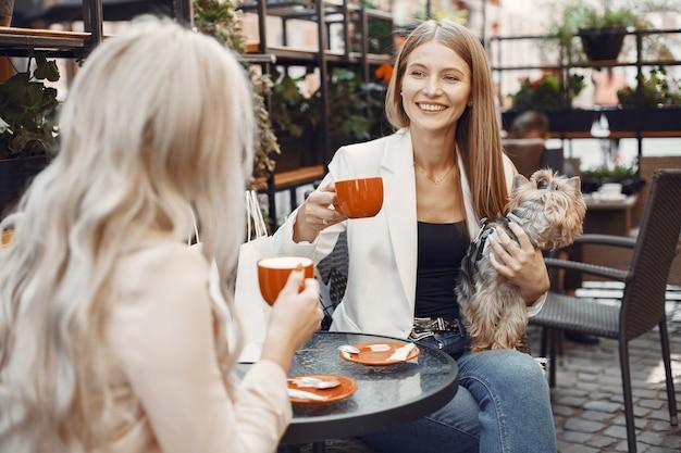 숙녀분들은 커피를 마 십니다. 테이블에 앉아 여자입니다. 귀여운 강아지와 친구.