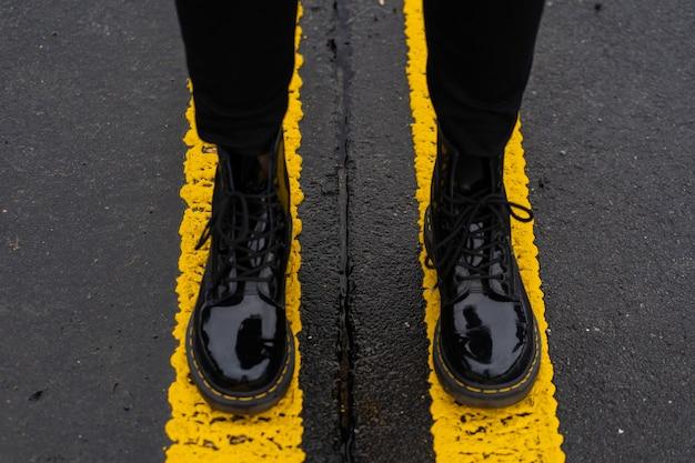 秋、春、アスファルトの道路に立っている女の子の足のレディースファッション革靴