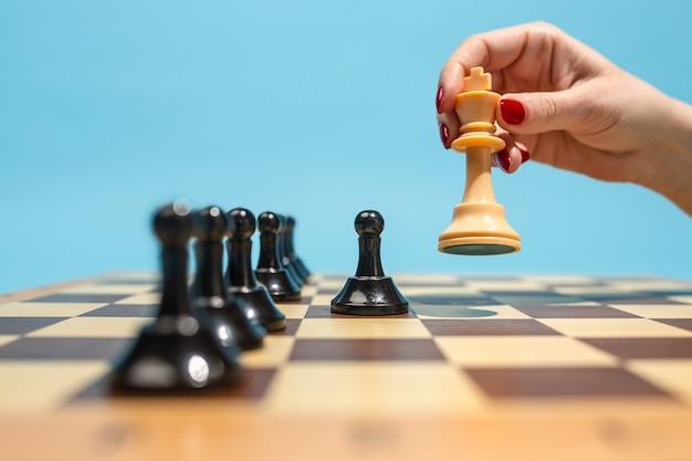 レディースファースト。チェス盤とゲームのコンセプト。ビジネスアイデア、競争、戦略、新しいアイデアの概念。青い背景のチェスの駒。セレクティブフォーカス。側面図。勝利、勝利、勝者の概念