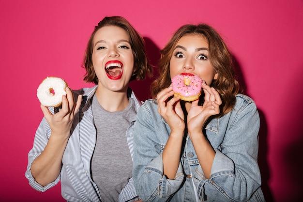 Ladies friends eating donuts