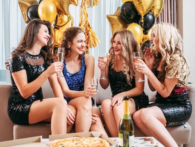 一緒に楽しんだり、笑ったり、ワインを飲んだり、装飾された部屋で特別なイベントを祝ったりする女性たち。