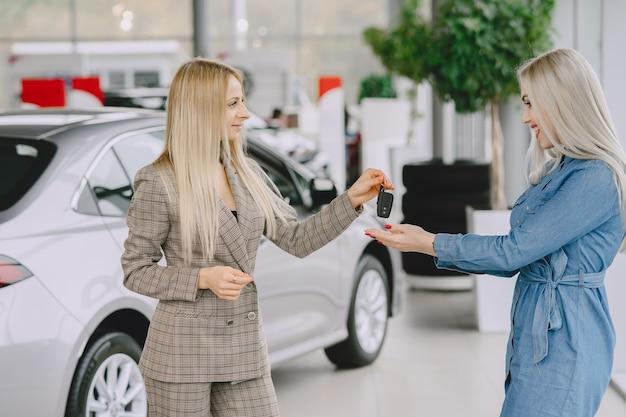 カーサロンの女性。車を買う女性。青いドレスを着たエレガントな女性。マネージャーはクライアントにキーを渡します。