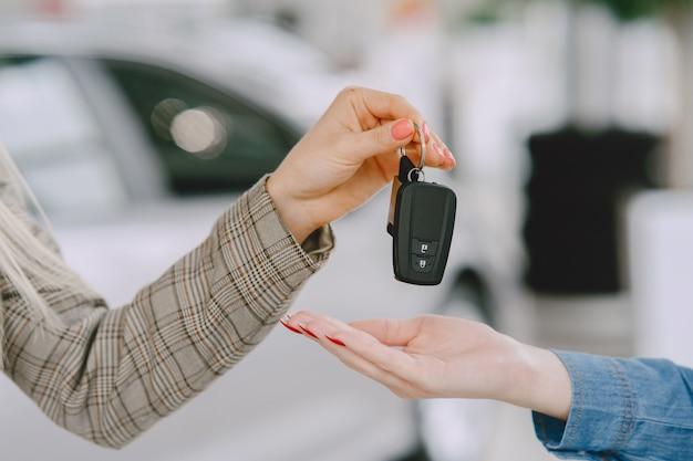 자동차 살롱의 숙녀. 차를 사는 여자. 파란 드레스에 우아한 여자입니다. 관리자는 클라이언트에게 키를 제공합니다.