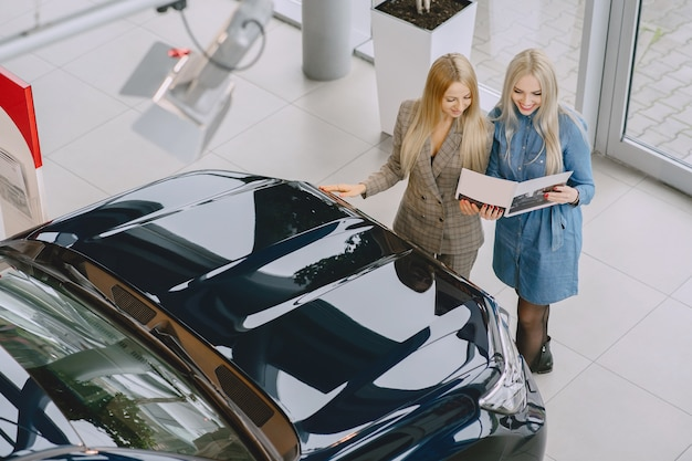 カーサロンの女性。車を買う女性。青いドレスを着たエレガントな女性。マネージャーはクライアントを支援します。