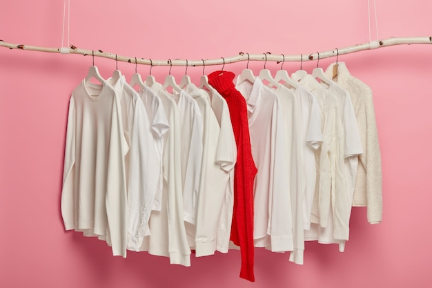 Ladies white casual clothes arranged on hangers, red knitted warm sweater stands out of whole collection. dressing set hanging against pink background. home wardrobe. classic style. fashion shop
