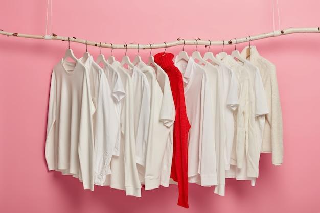 옷걸이에 배치 된 숙녀 흰색 캐주얼 의류, 빨간색 니트 따뜻한 스웨터가 전체 컬렉션에서 두드러집니다. 분홍색 배경에 매달려 드레싱 세트입니다. 홈 옷장. 클래식 스타일. 패션 숍