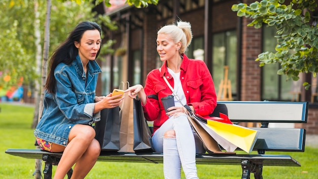 Ladies with shopping packets looking at smartphone on bench