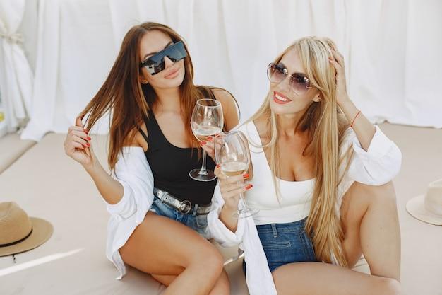 Дамы с виноградной лозой. девушки в топе и шортах. друзья в солнечных очках.