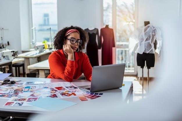 레이디 적극적으로 생각합니다. 작업 스튜디오에 머무는 동안 노트북과 함께 시간을 보내는 바쁜 곱슬 머리 디자이너