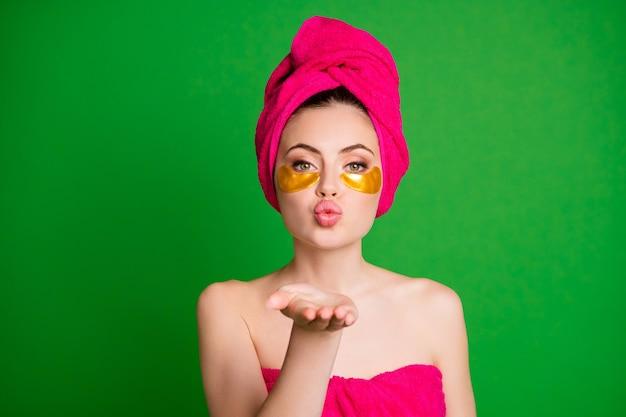 目のパッチの下でシャワーを使用した後の女性は、カメラウェアタオルにエアキスを送信します体の頭は緑色の背景を分離しました