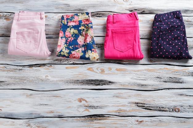 Брюки женские разного цвета. брюки темно-синего и светло-розового цвета. привлекательные скидки в магазине одежды. пора идти по магазинам.