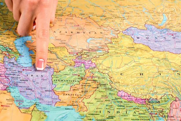 女性の指はイランを指しています。地図上でイランを示す女性。地理の授業で。それらの遠い国の1つ。