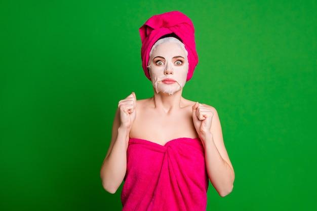 Леди применяет маску для лица с испуганными глазами, парень видит ее без макияжа, полотенца, тело, голова, изолированный зеленый цвет фона