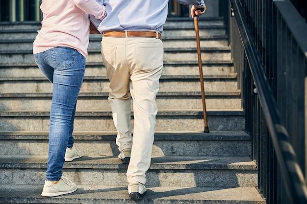 계단을 오르는 남자를 돕는 여자