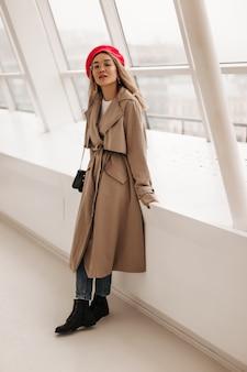 Signora in trench midi beige e berretto rosso con borsa a tracolla, in posa appoggiata su una grande finestra bianca