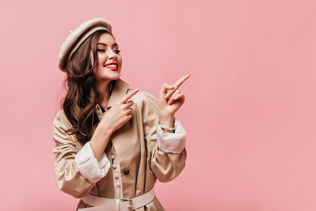 Lady in beige trench coat is smiling and pointing her fingers at pink background with space for text.