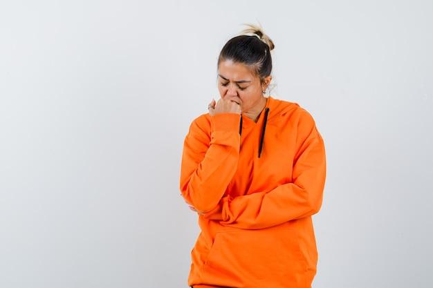 오렌지색 후드티를 입고 감정적으로 주먹을 물고 우울해 보이는 여성