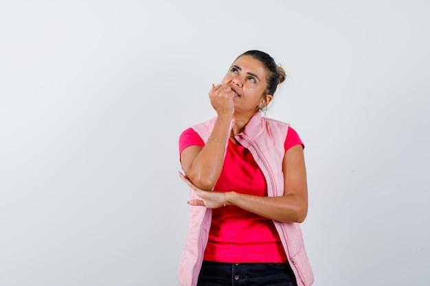 Signora che si mangia le unghie in maglietta, canottiera e sembra sognante